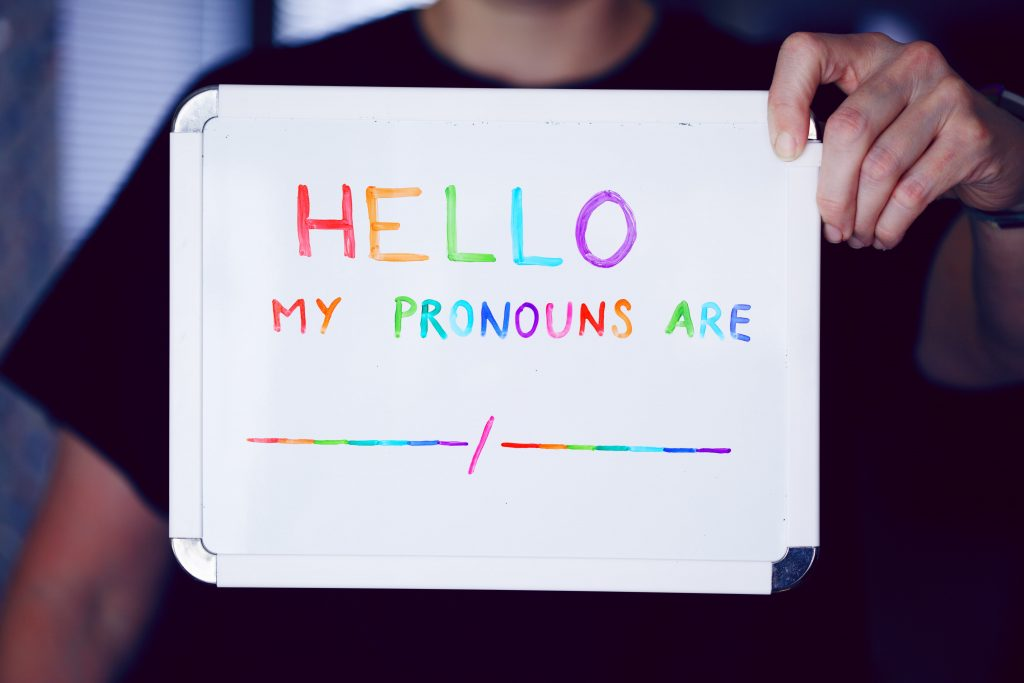 Person holding up sign with the text 'Hello my pronouns are....'